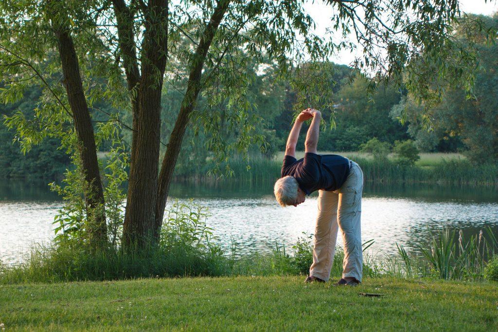 Älterer Mann bei der Gymnastik im Freien.